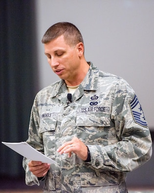 U.S. Air Force Chief Master Sgt. Steve Nichols, 60th Air Mobility Wing command chief, gives a briefing during a commander's call run by U.S. Air Force Col. John Klein, 60th AMW commander, at Travis Air Force Base, Calif., August 8, 2017. Klein and Nichols discussed a variety of topics to include safety, projecting American power and how every Airmen fits into the mission. (U.S. Air Force photo by Louis Briscese)