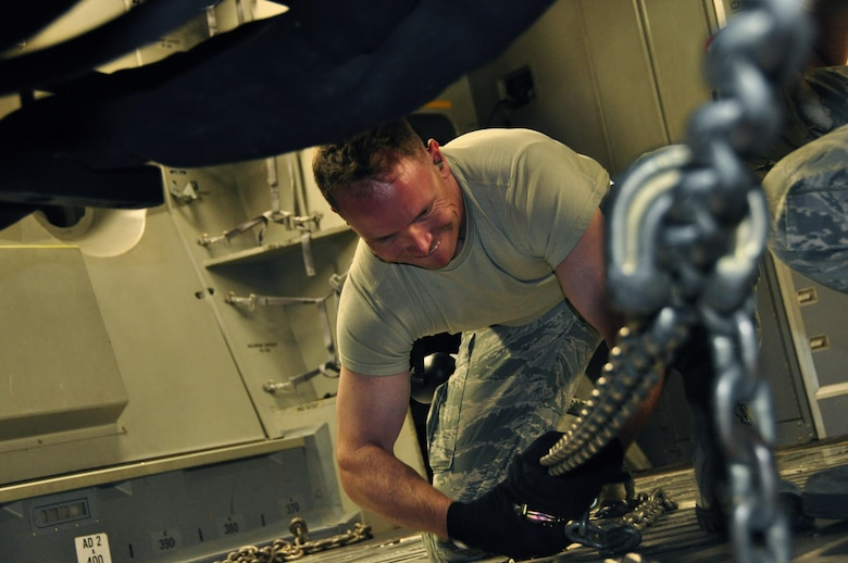 Staff Sgt. Erick Bohm, a 39th Aerial Port Squadron air transportation technician, uses a chain to attach a 6k forklift to the floor of a C-17 Globemaster on the Travis Air Force Base flightline, Calif., July 12, 2017.