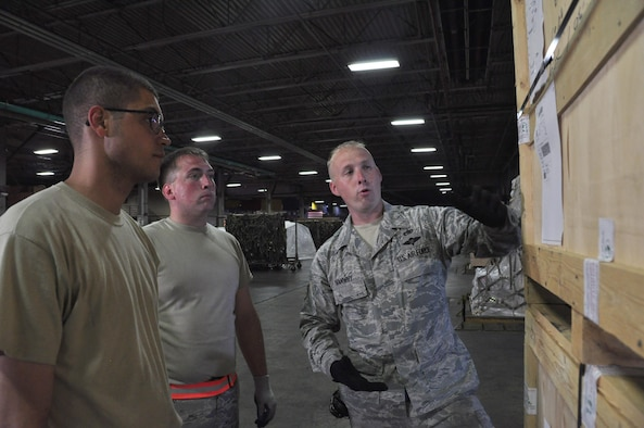 Staff Sgt. David Vanwhy, right, a 60th Aerial Port Squadron cargo operations shift supervisor, teaches Senior Airmen William Gates and Geoffery Piechowski, both 39th APS transportation technicians, how to ensure labels are properly marked and secured to cargo before being shipped off, at Travis Air Force Base, Calif., July 13, 2017. Gates and Piechowski are two of the 15 Reserve Citizen Airmen from the 39th APS, stationed at Peterson Air Force Base, Colo., who trained with their active duty counterparts at Travis AFB during an annual tour. (U.S. Air Force photo/Staff Sgt. Frank Casciotta)