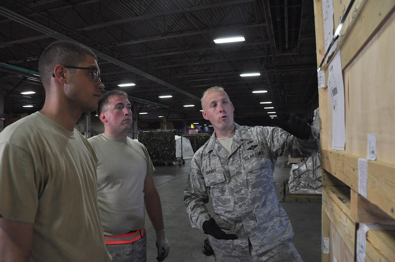 Staff Sgt. David Vanwhy, right, a 60th Aerial Port Squadron cargo operations shift supervisor, teaches Senior Airmen William Gates and Geoffery Piechowski, both 39th APS transportation technicians, how to ensure labels are properly marked and secured to cargo before being shipped off, at Travis Air Force Base, Calif., July 13, 2017.