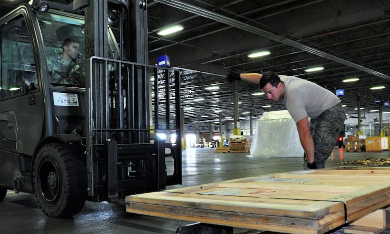 Senior Airman David Stevens, 60th Aerial Port Squadron, directs Senior Airman Nathan Jarvis, a 39th APS cargo processing technician and traditional reservist, on the use of a forklift as Jarvis manipulates heavy cargo at Travis Air Force Base, Calif., July 11, 2017.