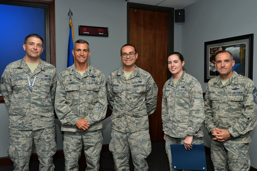 """U.S. Air Force Tech. Sgt. Anthony Olsen, left, Senior Airman Daniel Negron, center, and 1st Lt. Kimberlie Kirkpatrick, center right, 20th Aircraft Maintenance Squadron, 55th Aircraft Maintenance Unit """"Shooters"""" Airmen, are recognized as the Shaw """"Weasels of the Week"""" by Col. Daniel Lasica, 20th Fighter Wing (FW) commander, center left, and Chief Master Sgt. Daniel Hoglund, 20th FW command chief, at Shaw Air Force Base, S.C., Aug. 9, 2017. The Airmen received recognition for conducting aircraft sortie debriefs, which ensured accurate aircraft discrepancies were reported. Kirkpatrick accepted the award on behalf of fellow """"Shooters"""" Airmen, Staff Sgt. Nathan Housenga and Senior Airman Brandon Hamilton. (U.S. Air Force photo by Senior Airman Ashley Maldonado)"""