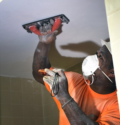 A Mobile District contractor works to renovate a dorm room, part of $9.7 million project to upgrade two old Army barracks on the former Ft. McClellan grounds.