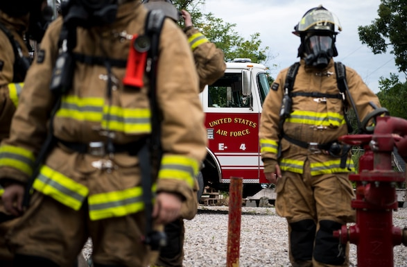 U.S. Air Force Firefighters from the 130th Airlift Wing Fire and Emergency Services prepare to enter a simulated house fire for training Aug. 6, 2017, at Emergency Preparedness Training Center, Institute, W.Va. The EPTC is a series of shipping containers with various pits, objects and places that plywood is attached to simulate a house fire. (U.S. Air National Guard Photo by Airman Caleb M. Vance)