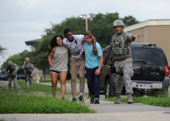 "Master Sgt. Michael Hurley, 81st Security Forces Squadron flight chief, guides Airmen portraying ""victims"" to a triage area during an antiterrorism and Force Protection Condition exercise, Aug. 3, 2017, on Keesler Air Force Base, Miss. The scenario included a gate runner who plowed into a student formation causing mass casualties. Wing and safety personnel designed the exercise to prepare Keesler personnel for potential real world situations. (U.S. Air Force photo by Kemberly Groue)"