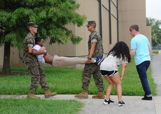 "U.S. Marine Corps Lance Corporal Daniel Jarvis and Private 1st Class Roberto Moreno, Keesler Marine Detachment students, assist ""victims"" injured during an antiterrorism and Force Protection Condition exercise, Aug. 3, 2017, on Keesler Air Force Base, Miss. The scenario included a gate runner who plowed into a student formation causing mass casualties. Wing and safety personnel designed the exercise to prepare Keesler personnel for potential real world situations. (U.S. Air Force photo by Kemberly Groue)"