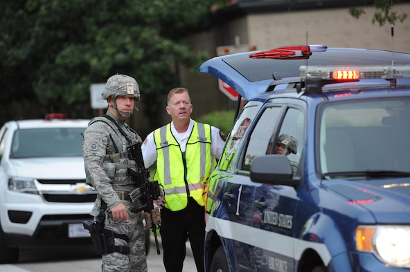 Senior Master Sgt. Richard Crim, 81st Security Forces Squadron manager, and Gary Pierson, 81st Infrastructure Division deputy fire chief, observe on-scene activity during an antiterrorism and Force Protection Condition exercise, Aug. 3, 2017, on Keesler Air Force Base, Miss. The scenario included a gate runner who plowed into a student formation causing mass casualties. Wing and safety personnel designed the exercise to prepare Keesler personnel for potential real world situations. (U.S. Air Force photo by Kemberly Groue)