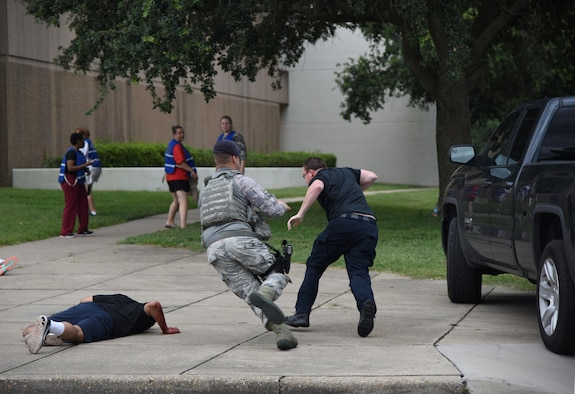 Staff Sgt. Tyler Chambers, 81st Security Forces Squadron military working dog handler, chases Officer Jeremy Ellzey, 81st SFS police officer supervisor, as he portrays the gate runner during an antiterrorism and Force Protection Condition exercise, Aug. 3, 2017, on Keesler Air Force Base, Miss. During the scenario Ellzey ran the base gate and plowed into a student formation causing mass casualties. Wing and safety personnel designed the exercise to prepare Keesler personnel for potential real world situations. (U.S. Air Force photo by Kemberly Groue)