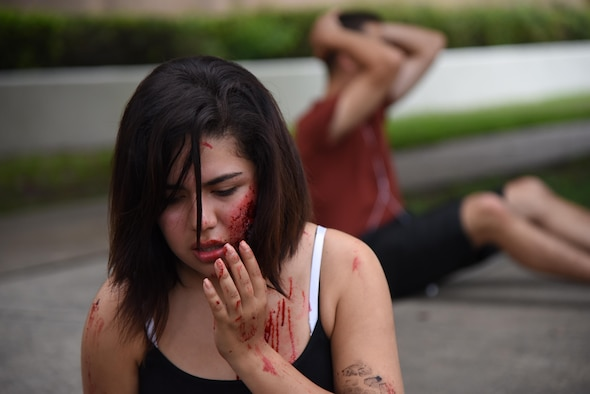 "Airman Basic Stephanie Gonzalez, 335th Training Squadron student, portrays a ""victim"" injured during an antiterrorism and Force Protection Condition exercise, Aug. 3, 2017, on Keesler Air Force Base, Miss. The scenario included a gate runner who plowed into a student formation causing mass casualties. Wing and safety personnel designed the exercise to prepare Keesler personnel for potential real world situations. (U.S. Air Force photo by Kemberly Groue)"
