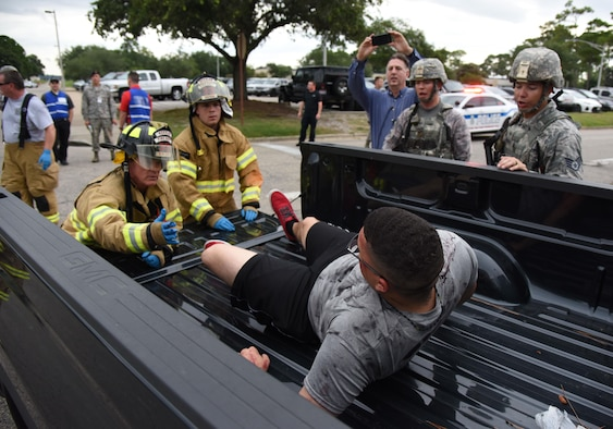 "Keesler first responders assist Airman 1st Class Esteban Cruz, 335th Training Squadron student, as he portrays a ""victim""  injured during an antiterrorism and Force Protection Condition exercise, Aug. 3, 2017, on Keesler Air Force Base, Miss. The scenario included a gate runner who plowed into a student formation causing mass casualties. Wing and safety personnel designed the exercise to prepare Keesler personnel for potential real world situations. (U.S. Air Force photo by Kemberly Groue)"