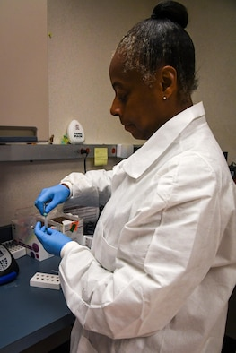 Master Sgt. Nordyica Woodfork, 2nd Medical Group laboratory technician, removes a specimen from a collected sample at Barksdale Air Force Base, La., Aug. 2, 2017. Barksdale's laboratory technicians collected over 154,819 specimens for analysis within the past 12 months, performing 118,192 tests locally within the medical group. (Photo/ Samantha Maiette)