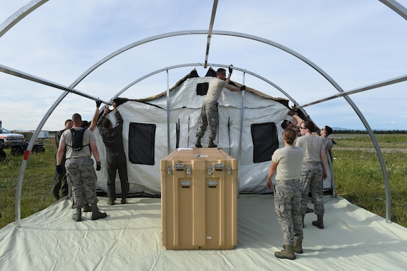 U.S. Airmen assigned to the 673rd Medical Group construct a tent during exercise Arctic ACE at Joint Base Elmendorf-Richardson, Alaska, July 9, 2017. This joint exercise was meant to test capabilities from an austere location to include setting up and operating a bare base while simultaneously establishing and maintaining communications with home station in order to meet new challenges or missions in a dynamic environment. (U.S. Air Force photo by Staff Sgt. Westin Warburton)