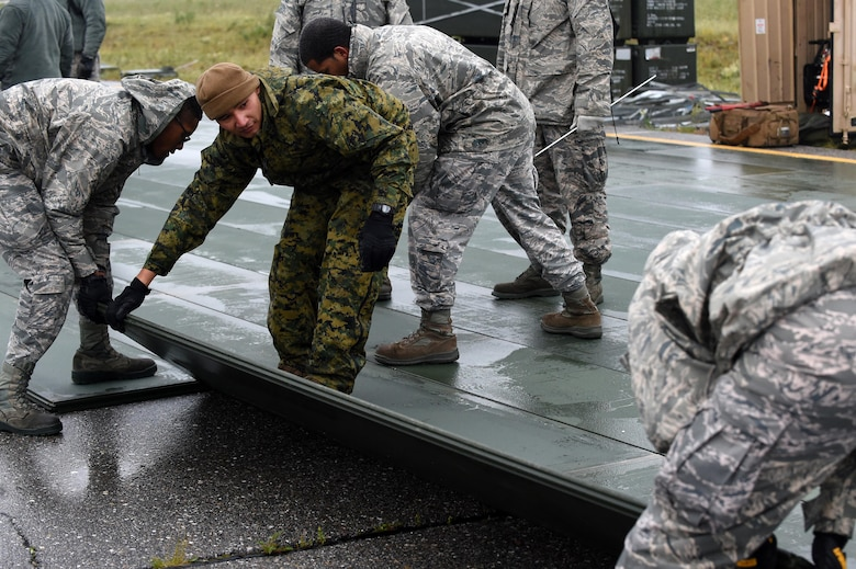 U.S. Marine Corps members with the 3rd Marine Aircraft Wing train Air Force Airmen on how to lay AM 2 matting down on damaged flight lines during exercise Arctic ACE, Alaska, July 11, 2017. The exercise included Airmen from the 3rd Wing, 673rd Air Base Wing, and 644th Combat Communications Squadron from Andersen, Air Base, Guam, as well as Marines from the 3rd Marine Aircraft Wing and U.S. Army in Alaska Soldiers, and focused on validating new ways to deploy and maneuver assets more fluidly during a crisis or conflict.