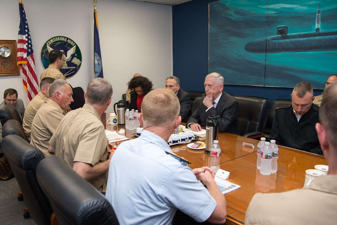 Defense Secretary Jim Mattis speaks to a group of sailors sitting around a table.