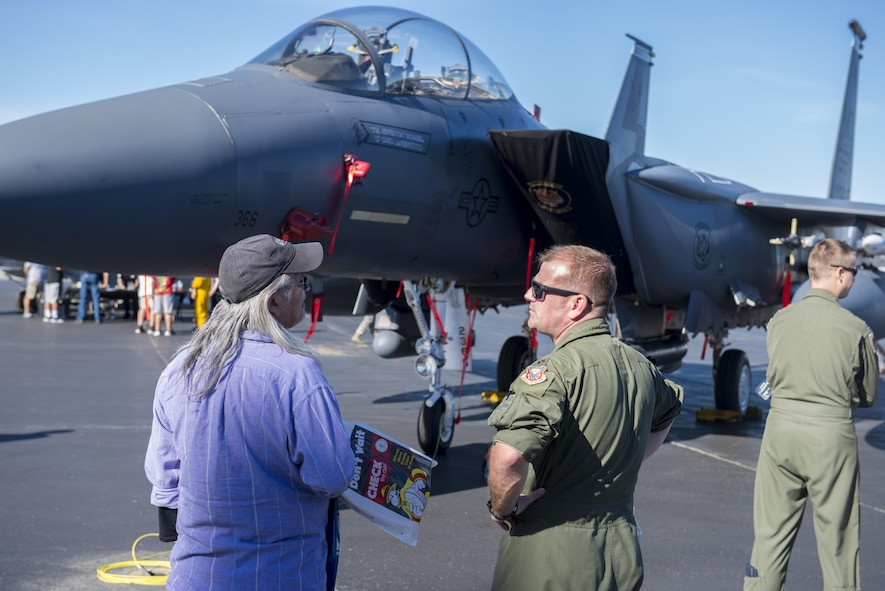 U.S. Air Force Maj. Ronald Davenport, an F-15E weapons system officer assigned to the 391st Fighter Squadron, Mountain Home Air Force Base (AFB), Idaho, speaks to a member of the local community during the Eielson AFB, Alaska, Open House, August 5, 2017. The event featured aircraft from multiple services and nations as well as presentations from the military working dogs and explosive ordnance disposal. (U.S. Air Force photo by Airman 1st Class Isaac Johnson)