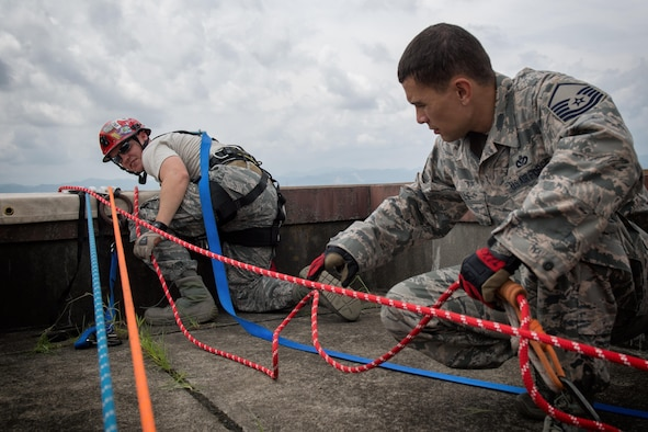 Airmen assigned to the 374th Civil Engineering Squadron assist Col. John Winkler, 374th Mission Support Group commander, rappel down a building, August 7, 2017, at Yokota Air Base, Japan. Firefighters participate in this type of training to maintain the necessary skills to respond to fire emergencies. (U.S. Air Force photo by Airman 1st Class Juan Torres)