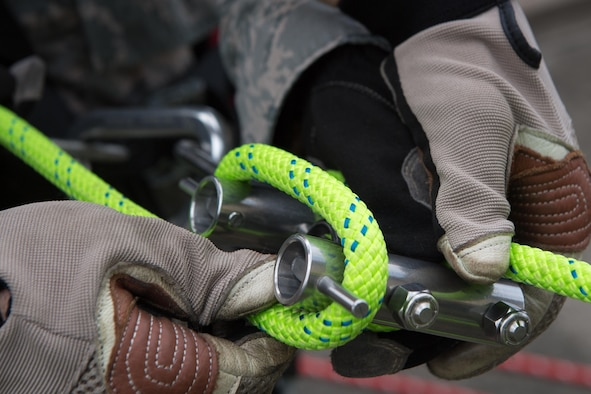 An Airman assigned to the 374th Civil Engineering Squadron secures rappelling equipment prior to its use, August 7, 2017, at Yokota Air Base, Japan. The equipment is used during high-angle rescues. (U.S. Air Force photo Airman 1st Class Juan Torres)