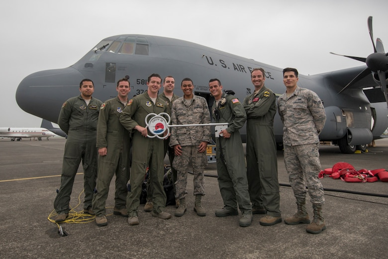 alt=Members of the C-130J delivery team pose for a photo in front of a C-130J Super Hercules