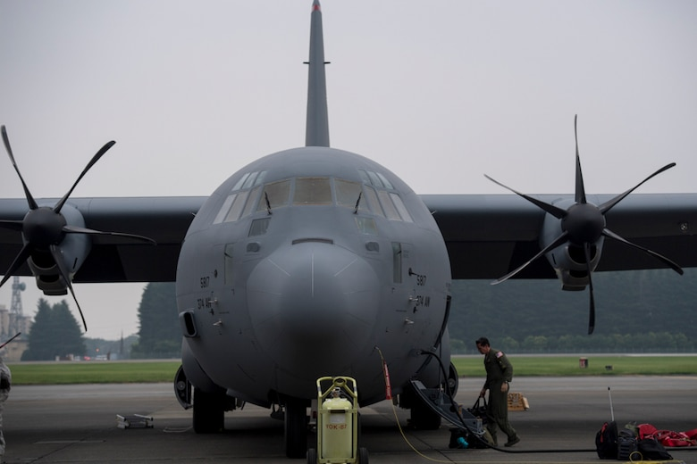 alt=Crew member from the 36th Airlift Squadron unloads luggage from a C-130J Super Hercules