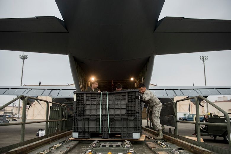 alt=Airman from the 374th Operations Group unload cargo from a C-130J Super Hercules