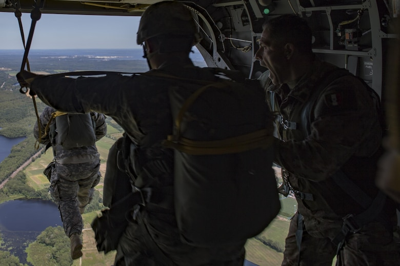 Italian army Lt. Gilberti Pier Luigi, jump master, instructs paratroopers to jump from a U.S. Army CH-47 Chinook during Leapfest, Aug. 6, 2017, in West Kingstown, R.I. The Rhode Island National guard hosted the 34th annual event, which is the largest international static line jump competition in the world. Team Moody's Airmen represented the only U.S. sister-service team and earned second place among 70 participating teams. (U.S. Air Force photo by Airman 1st Class Daniel Snider)
