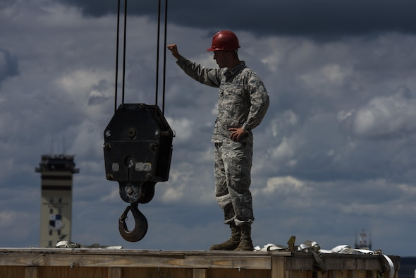 Airman 1st Class Nathaniel Norton, 52nd Civil Engineer Squadron heavy equipment operator, guides a crane into place to move parts for a replacement of an engine on a C-17 Globemaster III at Spangdahlem Air Base, Germany, Aug. 9, 2017. The 726th Air Mobility Squadron worked with the 52nd Logistics Readiness Squadron vehicle operations, 52nd Civil Engineer Squadron Dirt Boyz, and 721st Aircraft Maintenance Squadron in support of fixing the engine which takes an average of 12 hours to complete. (U.S. Air Force photo by Staff Sgt. Jonathan Snyder)