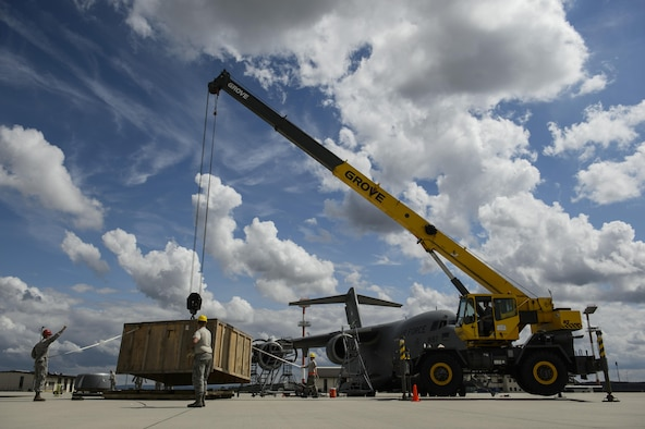 Airmen from the 726th Air Mobility Squadron work with 52nd Civil Engineer Squadron Dirt Boyz to move parts for replacing an engine on a C-17 Globemaster III at Spangdahlem Air Base, Germany, Aug. 9, 2017. The 726th AMS worked with the 52nd Logistics Readiness Squadron vehicle operations, 52nd CES Dirt Boyz, and 721st Aircraft Maintenance Squadron in support of fixing the engine which takes an average of 12 hours to complete. (U.S. Air Force photo by Staff Sgt. Jonathan Snyder)