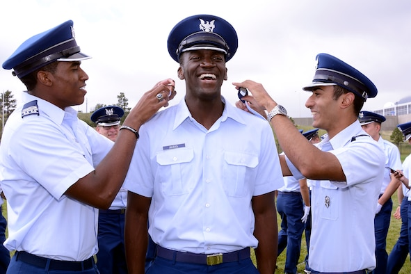 Senior-ranking cadets pin cadet-fourth-class rank on the uniform worn by a freshman cadet at the U.S. Air Force Academy, Aug. 9, 2017. The cadet is one of 1,280 young men and woman accepted into the Cadet Wing now that they've graduated Basic Cadet Training. (U.S. Air Force photo/Mike Kaplan)