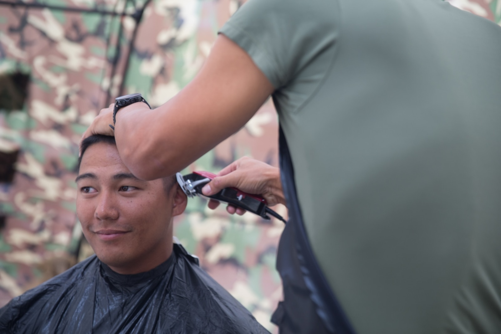 BRIDGEPORT, CALIF. - U.S. Navy LT. Mark Won, the chaplain for Combat Logistics Battalion 5, Combat Logistics Regiment 1, 1st Marine Logistics Group, cuts Second Lieutenant Karl Watje's hair during the Mountain Training Exercise 4-17 on the Marine Corps Mountain Warfare Training Center July 31, 2017. (U.S. Marine Corps photo by Lance Cpl. Timothy Shoemaker)