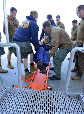 Petty Officer 1st Class Kim Nguyen (center) participates in a joint U.S. Coast Guard – U.S. Navy emergency plan extraction drill aboard the Coast Guard Cutter Healy in which the dive teams practice for and evaluate different cold water dive scenarios, July 22, 2017.  The Coast Guard's dive team depends on the Navy for use of their dive recompression chamber, a tool that helps to treat diving-related trauma. U.S. Coast Guard photo by Senior Chief Petty Officer Rachel Polish