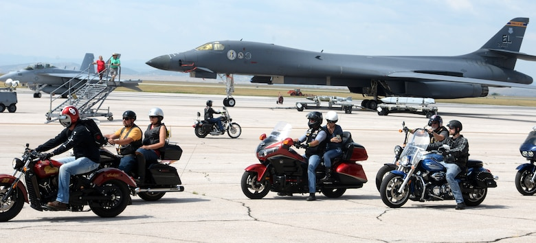 Motorcyclists pass by a B-1 bomber and an F-18 Super Hornet Aug 8, 2017 on the flight line at Ellsworth Air Force Base, S.D. The motorcycle ride ended at the Sturgis Veterans Appreciation Ceremony followed by with a flyover from a B-1 bomber over Main Street. (U.S. Air Force photo by Airman 1st Class Thomas Karol)