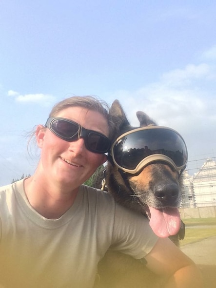 Staff Sgt. Amanda Cubbage, a 355th Security Forces Squadron member, poses for a photo with her military working dog, Rick, while assigned to Osan Air Base, South Korea. Cubbage was able to adopt Rick after he was retired due to old age. (Courtesy photo)