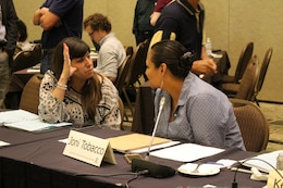 Catherine J. Warren, Native American consultation specialist, Omaha District, U.S. Army Corps of Engineers (left) and new MRRIC Tribal member Joni Tobacco, Ogalala Sioux Tribe (right) seated at a table.