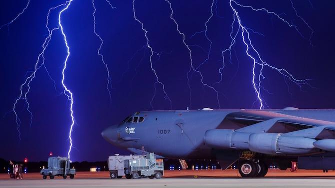 Lightning strikes behind an aircraft on a flight line.