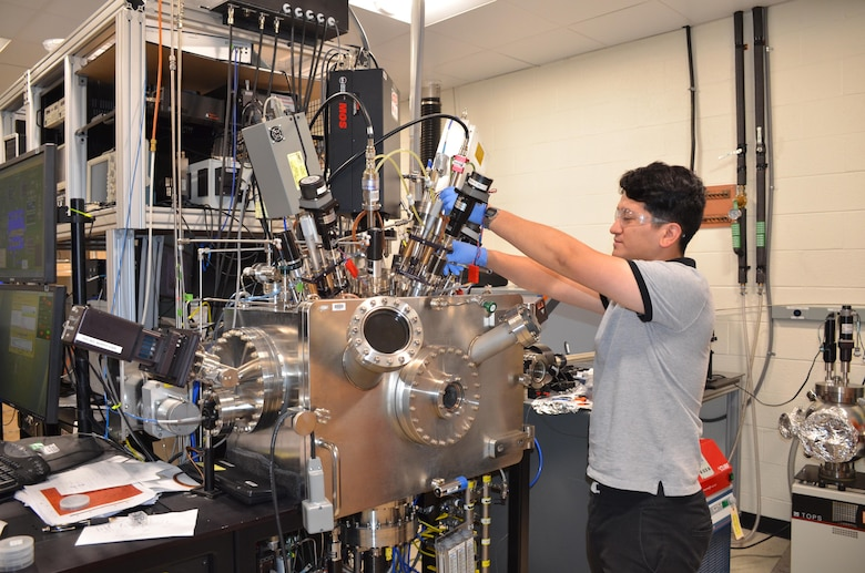 Graduate student from the University of Texas El Paso, Cristian Orozco, works in the Materials and Manufacturing Directorate over the summer. One of his duties includes working with a vacuum chamber for thin film coatings for optics.  (U.S. Air Force photo / Marisa Alia-Novobilski)