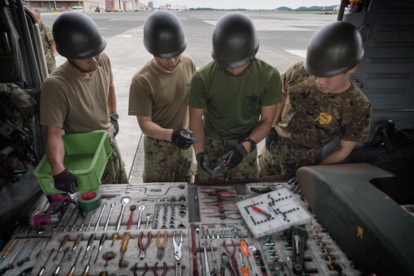 Japan Ground Self-Defense Force members assigned to the 102nd Aviation, at Camp Kizarazu, inspect tools prior to use, August 3, 2017, at Yokota Air Base, Japan. The tools were used to dismantle the aircraft during a C-17 load engagement. (U.S. Air Force photo by Airman 1st Class Juan Torres)
