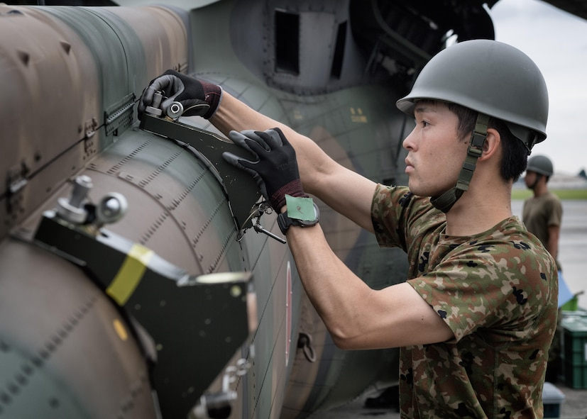 Japan Ground Self-Defense Force Sgt. Azusa Yamamoto, 102nd Aviation, at Camp Kizarazu, adjusts a tool on a UH-60JA helicopter during the dismantling of the aircraft, August 3, 2017, at Yokota Air Base, Japan. The dismantling was part of a C-17 load engagement between JGSDF and the U.S. Air Force. (U.S. Air Force photo by Airman 1st Class Juan Torres)