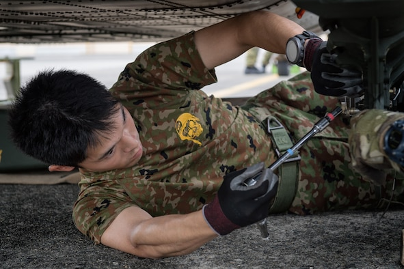 Japan Ground Self-Defense Force Sgt. Azusa Yamamoto, 102nd Aviation, at Camp Kizarazu, uses a tool on a UH-60JA helicopter during the dismantling of the aircraft, August 3, 2017, at Yokota Air Base, Japan. The dismantling was part of a C-17 load engagement between JGSDF and the U.S. Air Force. (U.S. Air Force photo by Airman 1st Class Juan Torres)