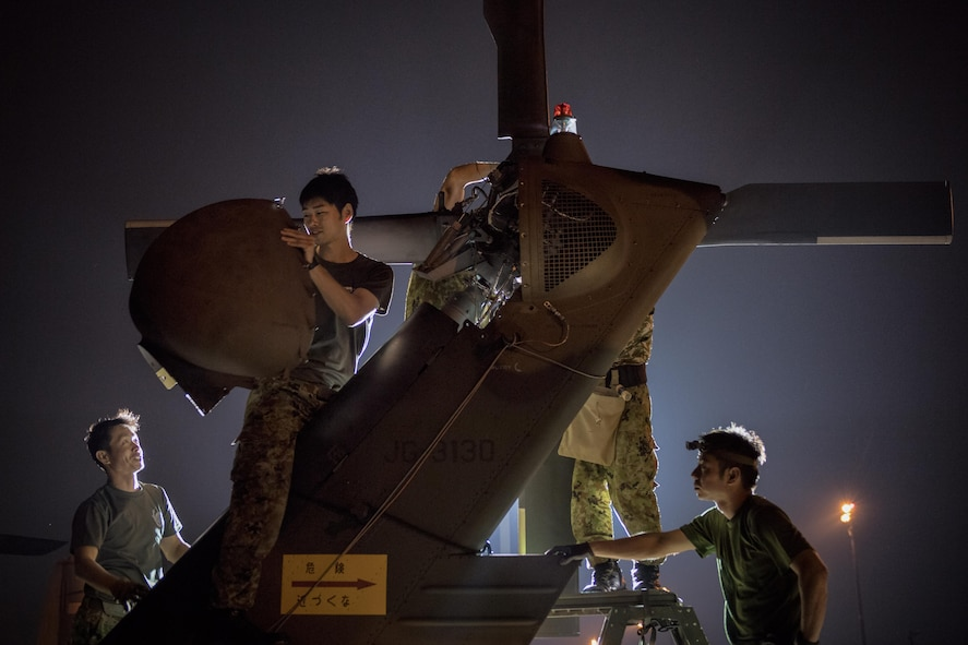 Japan Ground Self-Defense Force members assigned to the 102nd Aviation, Camp Kizarazu, work together to reassemble a UH-60JA helicopter, August 4, 2017, at Yokota Air Base, Japan. The helicopter was dismantled during a C-17 load engagement highlighting Pacific Air Force's interoperability with the JGSDF. (U.S. Air Force photo by Airman 1st Class Juan Torres)