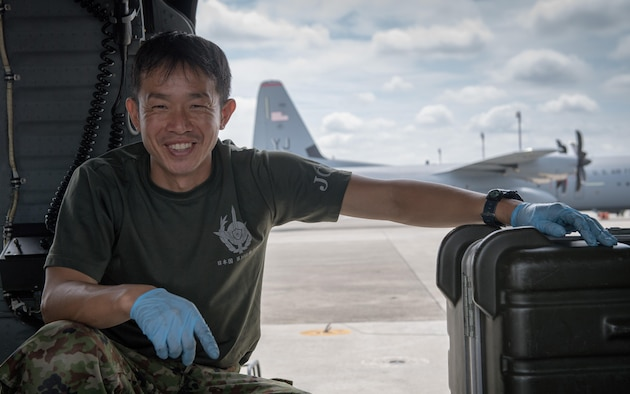 A Japan Ground Self-Defense Force member poses for a photo inside a UH-60JA helicopter during the dismantling of the aircraft, August 3, 2017, at Yokota Air Base, Japan. The dismantling was part of a C-17 load engagement between JGSDF and the U.S. Air Force. (U.S. Air Force photo by Airman 1st Class Juan Torres)