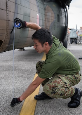 A Japan Ground Self-Defense Force member measures the opening under UH-60JA helicopter during a C-17 load engagement, August 4, 2017, at Yokota Air Base, Japan. The training highlighted Yokota's bilateral support and interoperability with the JGSDF. (U.S. Air Force photo by Airman 1st Class Juan Torres)