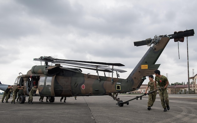 Japan Ground Self-Defense Force members assigned to the 102nd Aviation, at Camp Kizarazu, work together to move a UH-60JA helicopter during a C-17 load engagement, August 4, 2017, at Yokota Air Base, Japan. The training highlighted Yokota's bilateral support and interoperability with the JGSDF. (U.S. Air Force photo by Airman 1st Class Juan Torres)