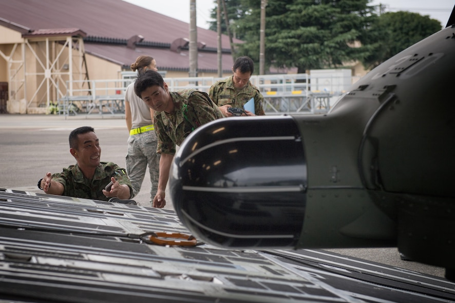 Japan Ground Self-Defense Force members inspect the opening under a UH-60JA helicopter prior to load during a C-17 load engagement, August 4, 2017, at Yokota Air Base, Japan. The training highlighted Yokota's bilateral support and interoperability with the JGSDF. (U.S. Air Force photo by Airman 1st Class Juan Torres)