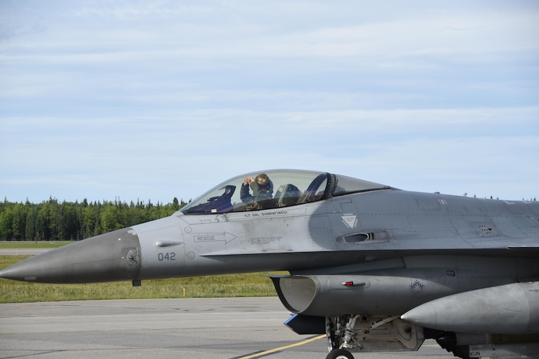 A U.S. Air Force F-16 Fighting Falcon pilot assigned to Kunsan Air Base, Republic of Korea, uses hand signals to communicate during Red Flag-Alaska at Eielson Air Force Base, Alaska, Aug. 2, 2017. RF-A provides an optimal training environment in the Indo-Asia Pacific region and focuses on improving ground, space and cyberspace combat readiness and interoperability of U.S. and international forces. (U.S. Air Force photo by Staff Sgt. Joshua Rosales)