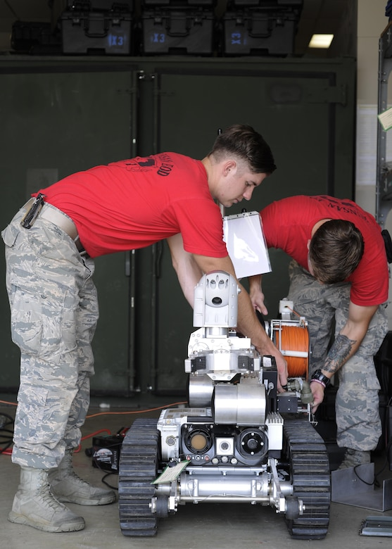 U.S. Air Force Airmen assigned to the 8th Civil Engineer Squadron Explosive Ordinance Disposal team, controls an Air Force Medium Sized Robot at Kunsan Air Base, Republic of Korea, Aug. 11, 2017. Airmen from both Osan Air Base and Kunsan Air Base, Republic of Korea had the opportunity to train with an instructor from Remotec, who supply and maintain AFMSRs and other robots for the Air Force, in rebuilding and repairing inoperable robots. (U.S. Air Force photo by Staff Sgt. Victoria H. Taylor)
