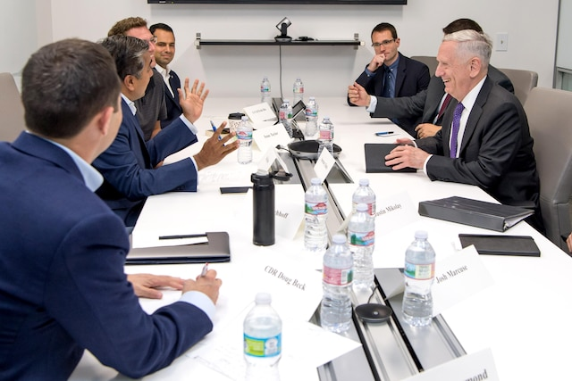 Defense Secretary Jim Mattis speaks to a group of people at a table.