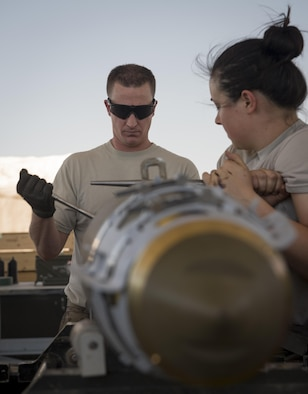 "Tech. Sgt. Chris Brunsman installs a tail fuse, as Staff Sgt. Ahbree Wetzel-Lee holds the bomb body steady at Bagram Airfield, Afghanistan, Aug. 4, 2017. Brunsman and Wetzel-Lee are munitions systems specialists, commonly referred to as ""AMMO,"" assigned to the 455th Expeditionary Maintenance Squadron. (U.S. Air Force photo by Staff Sgt. Benjamin Gonsier)"