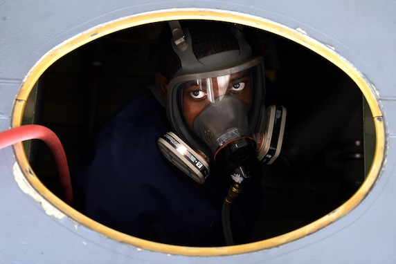 Senior Airman Stefan Stephenson-Shipp, 19th Maintenance Squadron fuel systems journeyman, enters a C-130J dry bay to reinstall a fuel manifold August 8, 2017, at Little Rock Air Force Base, Ark. All personnel entering a fuel tank or dry bay with open fuel lines are required to have a supplied air respirator on to prevent exposure to fumes. (U.S. Air Force photo/Airman 1st Class Kevin Sommer Giron)