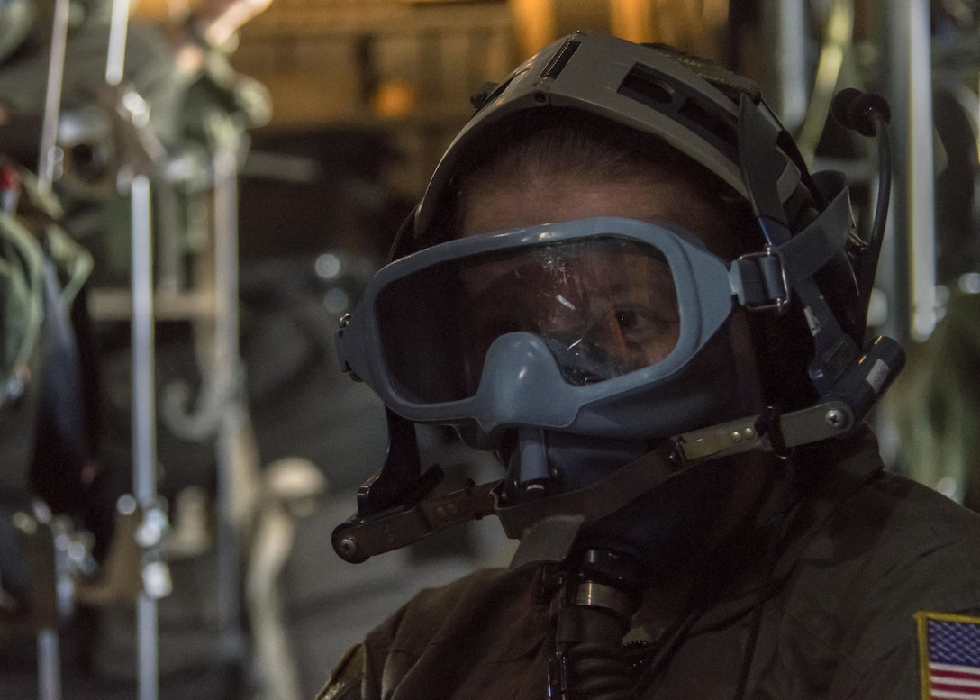 Tech. Sgt. Katherine Henson, 94th Aeromedical Evacuation Squadron flight medic, dons a firefighting mask and prepares to fight a simulated fire aboard a C-130H Hercules July 30, 2017. In case of a fire onboard the aircraft, one flight medic will fight the fire, while the other medics move patients. (U.S. Air Force photo/Staff Sgt. Andrew Park)