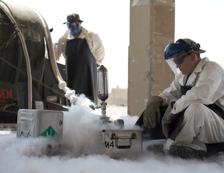 U.S. Air Force Staff Sgt. Kennie Delmo, left, a cryogenics supervisor and Senior Airman Samuel Fallot, a cryogenics journeyman with the 379th Expeditionary Logistics Readiness Squadron, Fuels Management Flight, fill a cryogenics sampler at Al Udeid Air Base, Qatar, Aug. 9, 2017.